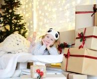 De jonge zitting die van het babymeisje dichtbij de magische Nieuwe giften van de jaarambacht door een Kerstboom dromen Stock Afbeelding