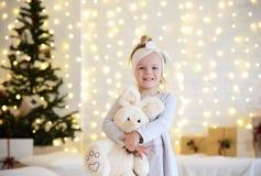 De jonge zitting die van het babymeisje dichtbij de magische Nieuwe giften van de jaarambacht door een Kerstboom dromen Royalty-vrije Stock Foto