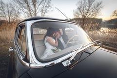 De jonge zitting die van het huwelijkspaar binnen retro auto glimlachen en kust elkaar enkel gehuwd omhels koestert binnenauto Br stock foto