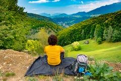 De jonge zitting van de bergwandelaar op een waterdichte nylon deken in een mooi berg landschap en het genieten van de van mening stock foto's