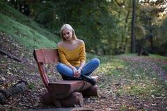 De jonge zitting van de blondevrouw alleen op een houten bank in bos, droevig en eenzaam stock afbeelding