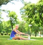 De jonge zitting van de atletenvrouw op een excercising mat en het uitrekken zich Stock Foto's