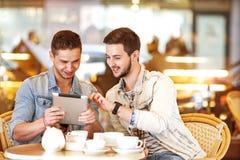 De jonge zitting van de hipsterkerel in een en koffie die coffe babbelt drinkt Royalty-vrije Stock Fotografie