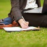 De jonge zitting van de manier mannelijke student op gras Stock Afbeeldingen