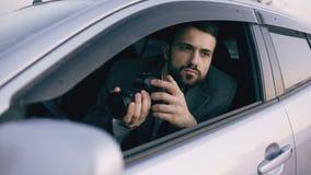 De jonge zitting van de privé-detectivemens binnen auto en het fotograferen met dslrcamera stock video