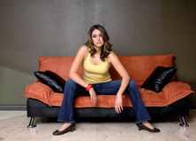 De jonge Zitting van de Vrouw op Bank royalty-vrije stock foto
