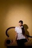 De jonge zitting van de vrouwen donkerbruine vrouw op bank Stock Foto