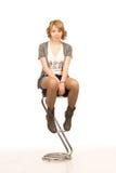 De jonge zitting van het blondemeisje op een barkruk Royalty-vrije Stock Fotografie