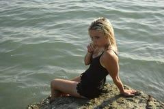 De jonge zitting van het blondemeisje op een steenplak in een overzees van Zonnige dag stock foto