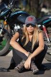 De jonge zitting van het fietsermeisje voor een motorfiets royalty-vrije stock foto