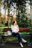 De jonge zitting van het gebruikssmartphone van de studentenvrouw op bank in het Park Royalty-vrije Stock Foto