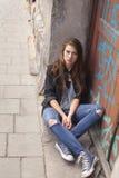 De jonge zitting van het hipstermeisje op de straat gang stock foto