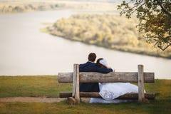 De jonge zitting van het huwelijks romantische paar op houten bank openlucht op natuurlijke achtergrond royalty-vrije stock foto