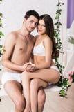De jonge zitting van het liefdepaar op de schommeling royalty-vrije stock foto's