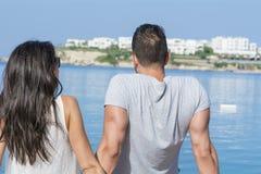 De jonge zitting van het liefdepaar op het strand die het overzees kijken Stock Foto's