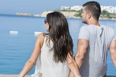 De jonge zitting van het liefdepaar op het strand die het overzees kijken Stock Foto