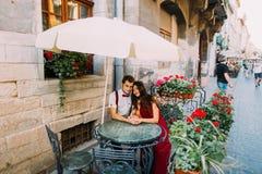 De jonge zitting van het manier elegante modieuze paar in de van de de zomerkoffie en holding handen Mooie zonnige dag stock afbeelding