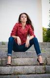 De jonge zitting van het maniermeisje op treden Royalty-vrije Stock Foto's