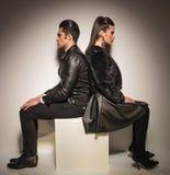 De jonge zitting van het manierpaar op een witte lijst Royalty-vrije Stock Fotografie