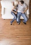 De jonge Zitting van het Paar bij het Kussen van de Zetel van de Liefde Stock Fotografie