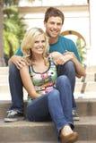 De jonge Zitting van het Paar op Stappen van de Bouw royalty-vrije stock foto
