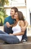 De jonge Zitting van het Paar op Stappen van de Bouw stock fotografie