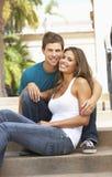 De jonge Zitting van het Paar op Stappen van de Bouw stock foto's