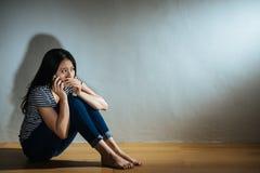 De jonge zitting van het slachtoffermeisje op houten vloer Royalty-vrije Stock Foto's