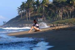 De jonge zitting van het surfermeisje op het strand tijdens zonsondergang stock fotografie