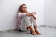 De jonge zitting van het tienermeisje op de vloer door de muur die - a kijken royalty-vrije stock afbeeldingen