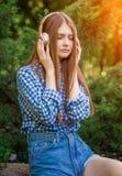 De jonge zitting van het vrouwen leuke donkerbruine meisje op steenhoofdtelefoons Royalty-vrije Stock Foto