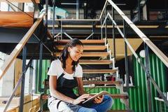 De jonge zitting van de koffieeigenaar op trap royalty-vrije stock foto