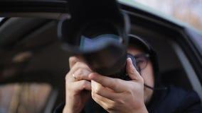 De jonge zitting van de privé-detectivemens binnen auto en het fotograferen met dslrcamera stock videobeelden