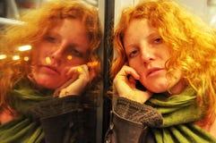 De jonge zitting van de roodharige mooie sexy vrouw zorgvuldig in een bewegende trein wordt het portret weerspiegeld in het venst stock foto's