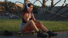 De jonge zitting van de skateboardervrouw en zet op hoofdtelefoons stock video