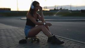 De jonge zitting van de skateboardervrouw en zet op hoofdtelefoons stock footage