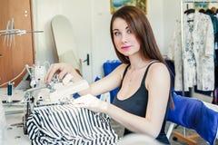 De jonge zitting van de vrouwennaaister en naait op naaimachine Het naaisterwerk aangaande de naaimachine Kleermaker die een kled Royalty-vrije Stock Afbeeldingen