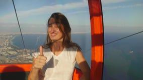 De jonge zitting van de vrouwentoerist in kabelwagen op de manier tot de bovenkant van Kunektepe Teleferik stock footage