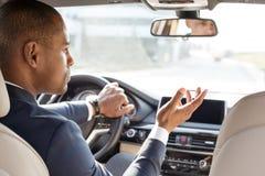 De jonge zitting van de zakenmanbestuurder binnen auto die opzij voertuigen bekijken betrof achterbankmening stock fotografie