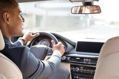 De jonge zitting van de zakenmanbestuurder binnen auto die opzij vrolijke achterbankmening kijken royalty-vrije stock foto's