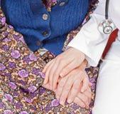 De jonge zoete arts houdt de hand van de oude vrouw Royalty-vrije Stock Foto