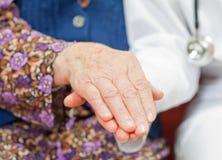 De jonge zoete arts houdt de hand van de oude vrouw Stock Afbeelding