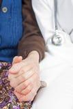 De jonge zoete arts houdt de hand van de oude vrouw Royalty-vrije Stock Afbeeldingen