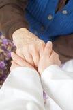 De jonge zoete arts houdt de hand van de oude vrouw Stock Fotografie