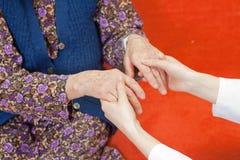 De jonge zoete arts houdt de hand van de oude vrouw Royalty-vrije Stock Foto's