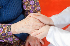 De jonge zoete arts houdt de hand van de oude vrouw Stock Foto