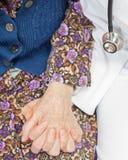 De jonge zoete arts houdt de hand van de oude vrouw Stock Foto's