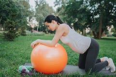 De jonge zwangere vrouw die van Nice training in park hebben Zij bevindt zich op knieën en kijkt neer Modelhelling aan grote oran royalty-vrije stock foto