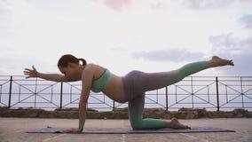 De jonge zwangere vrouw die yoga in two-legged lijst doen stelt in openlucht in ochtend stock videobeelden