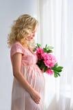 De jonge zwangere vrouw is met bloemen door het venster Royalty-vrije Stock Fotografie